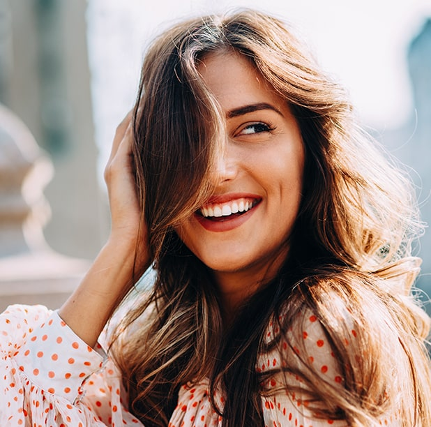 Woman smiling while flipping her hair
