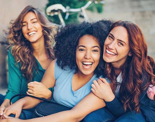 Young group of three women smiling outside