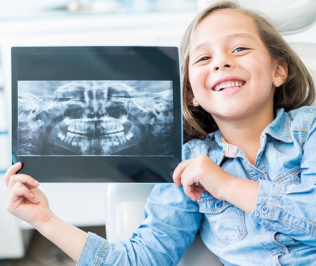 young girl holding her dental x-rays at the dentist's office