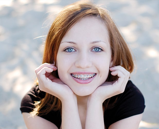 young redhead girl smiling with braces
