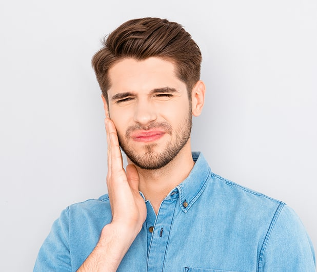 Young man with tooth pain holding his jaw