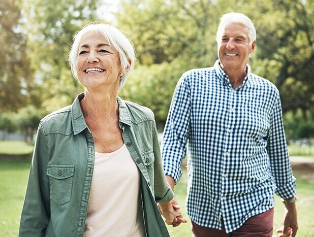 Older couple outside smiling in the park